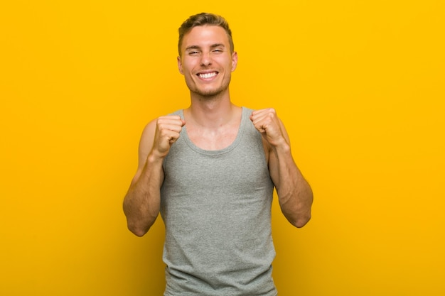Young caucasian sport man raising fist, feeling happy and successful