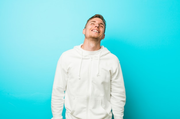 Young caucasian sport man relaxed and happy laughing, neck stretched showing teeth