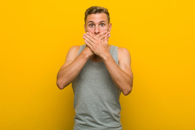 Young caucasian sport man shocked covering mouth with hands.