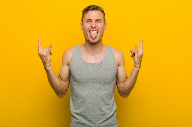 Young caucasian sport man showing rock gesture with fingers
