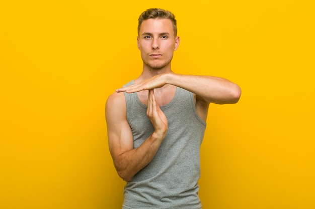 Young caucasian sport man showing a timeout gesture.