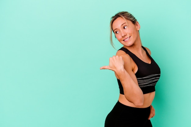 Young caucasian sport woman isolated on blue points with thumb finger away, laughing and carefree.