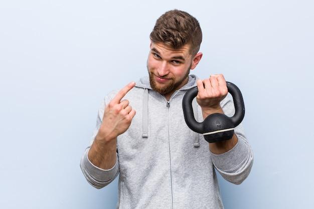 Молодой кавказский спортсмен держит гантель, указывая пальцем на вас, как будто приглашая подойти ближе.