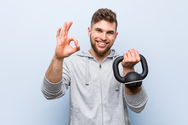 Young caucasian sportsman holding a dumbbell cheerful and confident showing ok gesture.