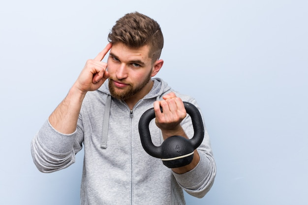 Young caucasian sportsman holding a dumbbell pointing his temple with finger, thinking, focused on a task.