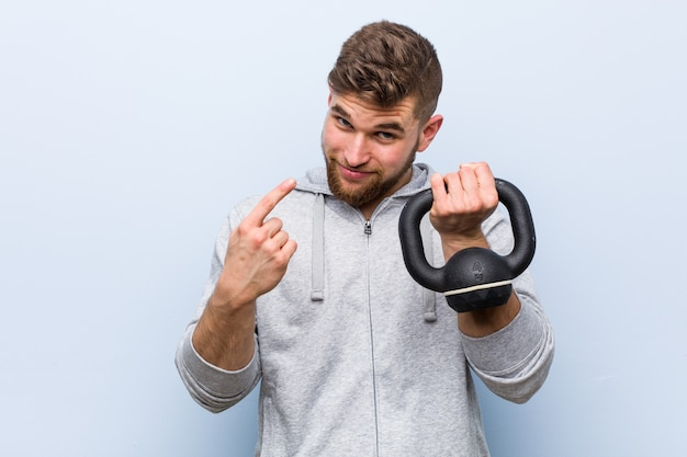 Young caucasian sportsman holding a dumbbell pointing with finger at you as if inviting come closer.