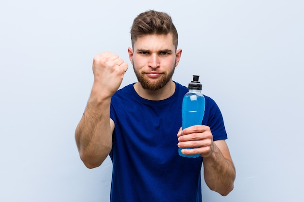 Young caucasian sportsman holding an isotonic drink showing fist to camera, aggressive facial expression.