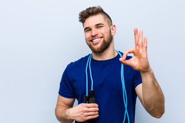 Young caucasian sportsman with a jump rope cheerful and confident showing ok gesture.