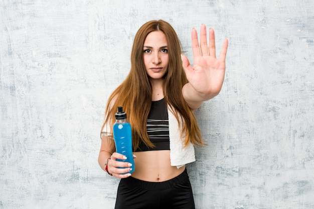 Young caucasian sportswoman holding a isotonic drink standing with outstretched hand showing stop sign