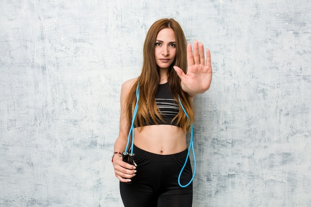 Young caucasian sportswoman holding a jump rope standing with outstretched hand showing stop sign, preventing you.