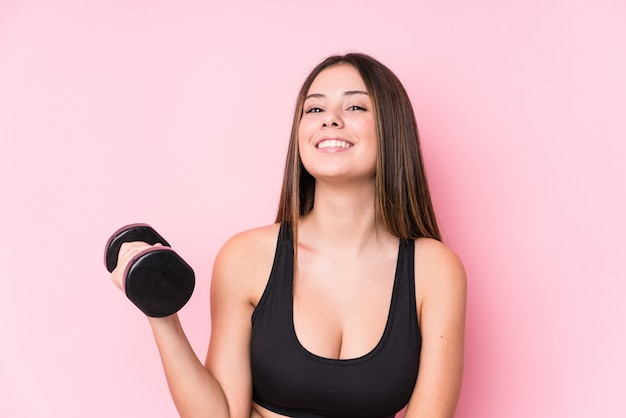 Young caucasian sporty woman holding a dumbbell