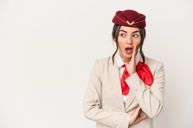 Young caucasian stewardess woman isolated on white background is saying a secret hot braking news and looking aside