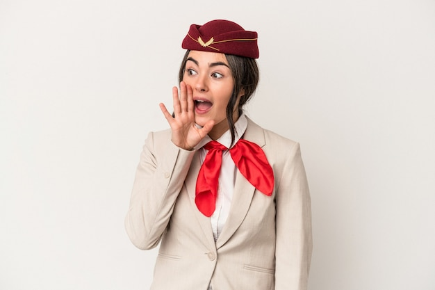 Young caucasian stewardess woman isolated on white background shouting and holding palm near opened mouth.