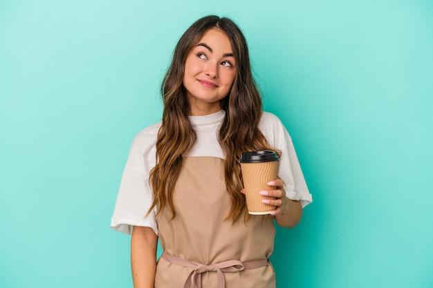 目標と目的を達成することを夢見て青い背景に分離されたテイクアウトコーヒーを保持している若い白人店員の女性