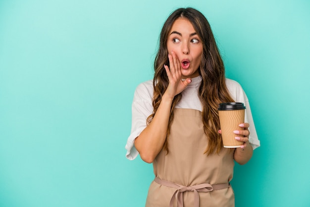 Young caucasian store clerk woman holding a takeaway coffee isolated on blue background is saying a secret hot braking news and looking aside