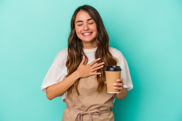 Young caucasian store clerk woman holding a takeaway coffee isolated on blue background laughs out loudly keeping hand on chest.