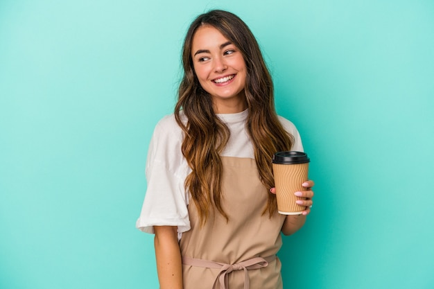 Young caucasian store clerk woman holding a takeaway coffee isolated on blue background looks aside smiling, cheerful and pleasant.