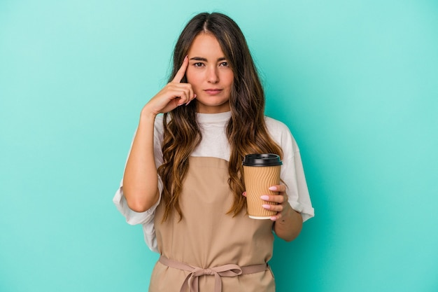 Young caucasian store clerk woman holding a takeaway coffee isolated on blue background pointing temple with finger, thinking, focused on a task.