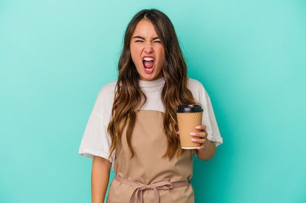 Young caucasian store clerk woman holding a takeaway coffee isolated on blue background screaming very angry and aggressive.
