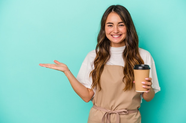 Young caucasian store clerk woman holding a takeaway coffee isolated on blue background showing a copy space on a palm and holding another hand on waist.