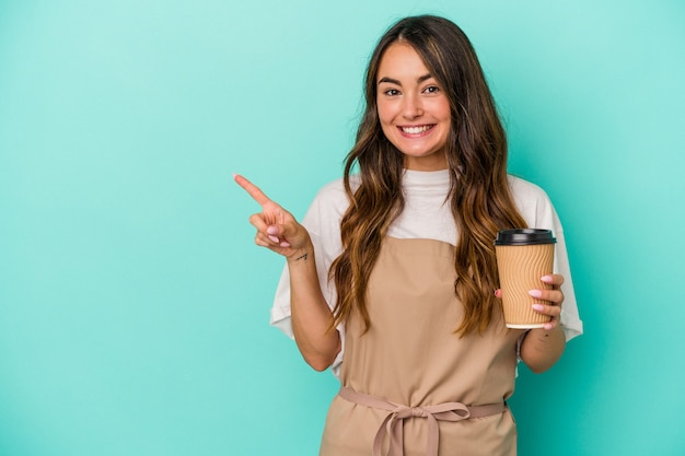 Young caucasian store clerk woman holding a takeaway coffee isolated on blue background smiling and pointing aside, showing something at blank space.