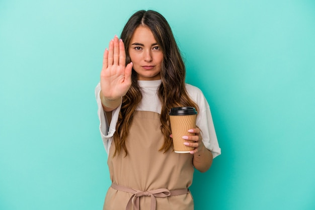 Young caucasian store clerk woman holding a takeaway coffee isolated on blue background standing with outstretched hand showing stop sign, preventing you.
