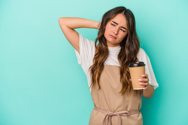 Young caucasian store clerk woman holding a takeaway coffee isolated on blue background touching back of head, thinking and making a choice.