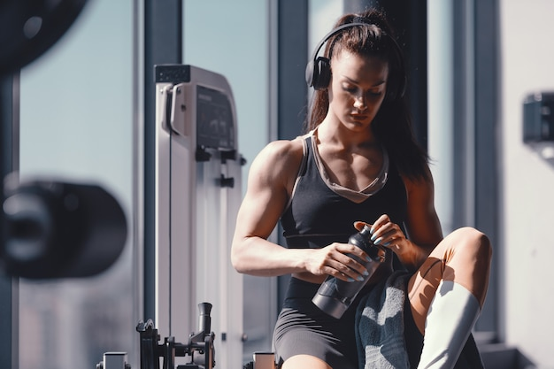 Young caucasian strong muscular female bodybuilder sitting in gym with headphones on ears and water in hands. suffer the pain of discipline of suffer the pain of regret.