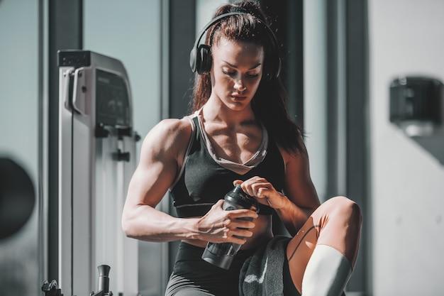若い白人の強い筋肉女性ボディービルダーは、耳にヘッドフォンと手で水でジムで座っています。専念してください、それは一晩で起こることはありません