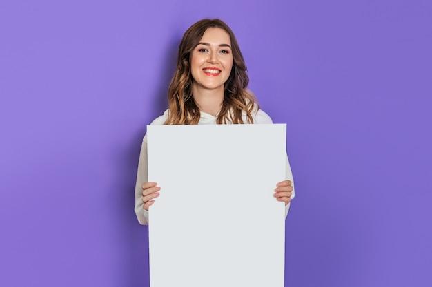 ライラックの背景に分離された笑顔の白い紙、ポスター、プラカードを手に持っている若い白人学生の女の子。コピースペース