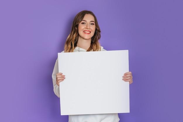 ライラックの背景で隔離の笑顔の手に白い正方形の紙のシートを保持している若い白人学生の女の子。コピースペース