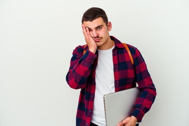 젊은 백인 학생 남자는 지루하고 피곤하고 긴장 하루가 필요한 흰색에 고립 된 노트북을 들고.