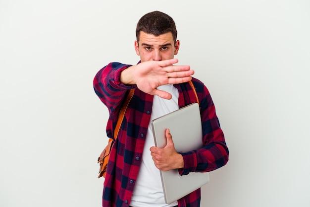 孤立したラップトップを保持している若い白人学生の男