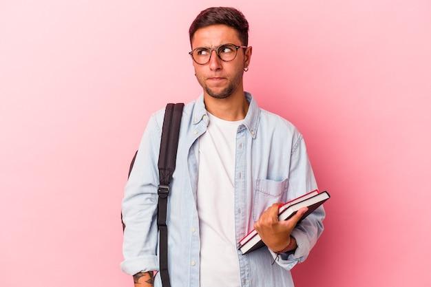 ピンクの背景に分離された本を持っている若い白人学生の男性は混乱し、疑わしく、不安を感じています。