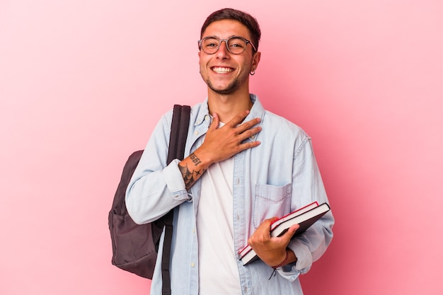 ピンクの背景に分離された本を持っている若い白人学生の男は、胸に手を置いて大声で笑います。