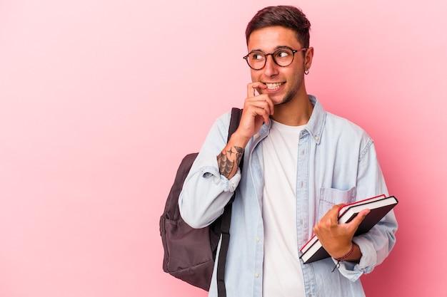 ピンクの背景に分離された本を持っている若い白人学生の男は、コピースペースを見ている何かについて考えてリラックスしました。