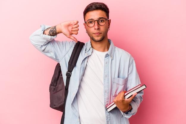 嫌いなジェスチャーを示すピンクの背景に分離された本を持っている若い白人学生の男は、親指を下に向けます。不一致の概念。