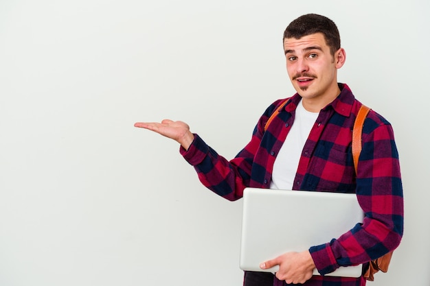 Young caucasian student man holding a laptop isolated on white background excited holding a copy space on palm.