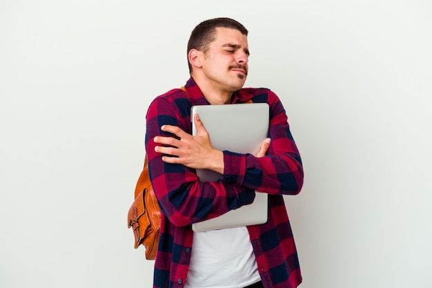 Young caucasian student man holding a laptop isolated on white background hugs, smiling carefree and happy.