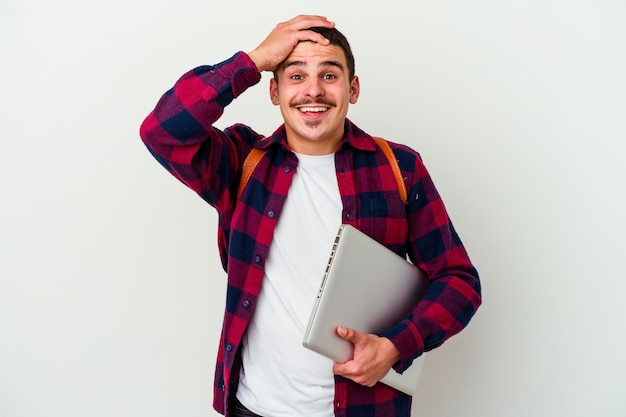 Young caucasian student man holding a laptop isolated on white background laughs joyfully keeping hands on head. happiness concept.