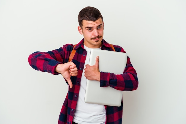 Young caucasian student man holding a laptop on white showing thumbs up and thumbs down, difficult choose concept