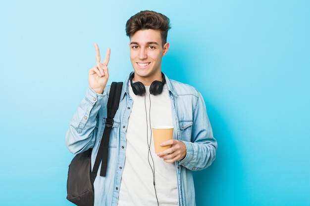 Young caucasian student man holding a take away coffee showing number two with fingers.