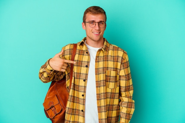 Young caucasian student man isolated on blue person pointing by hand to a shirt copy space, proud and confident