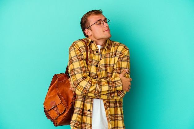 Young caucasian student man isolated on blue wall hugs, smiling carefree and happy.