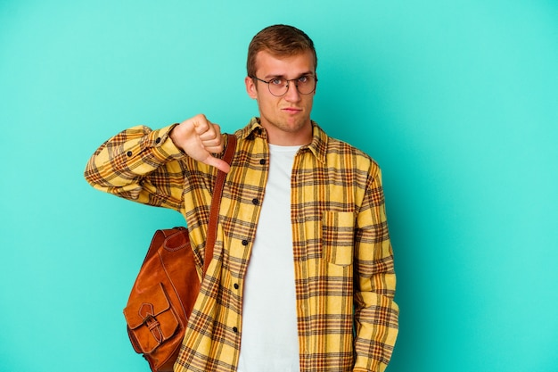 Young caucasian student man isolated on blue wall showing a dislike gesture, thumbs down. disagreement concept.