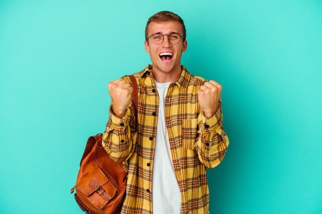평온하고 흥분 응원 파란색 배경에 고립 된 젊은 백인 학생 남자. 승리 개념.
