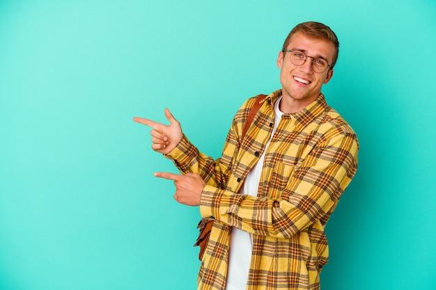 파란색 배경에 고립 된 젊은 백인 학생 남자 멀리 집게 손가락으로 가리키는 흥분.