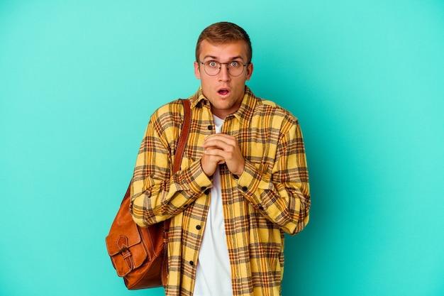 행운을 위해기도하는 파란색 배경에 고립 된 젊은 백인 학생 남자, 깜짝 놀라게하고 입을 앞으로 찾고 열기.