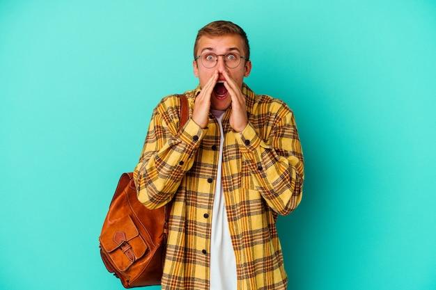 파란색 배경 앞에 흥분 소리에 고립 된 젊은 백인 학생 남자.