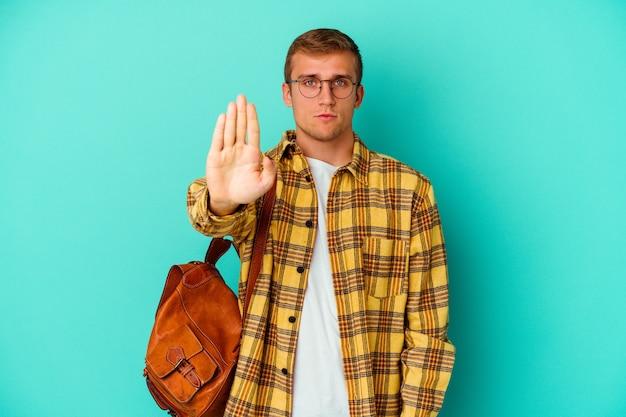 젊은 백인 학생 남자는 당신을 방지, 정지 신호를 보여주는 뻗은 손으로 서 파란색 배경에 고립.